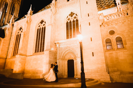 Beautiful bride spinning with perfect dress near great historical building