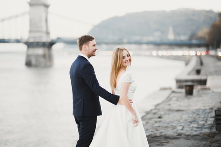 Wedding couple, groom and bride hugging, outdoor near river