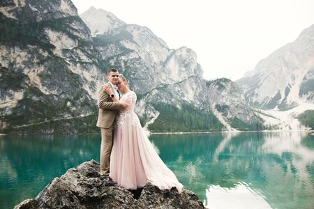 Wedding couple on the nature is hugging each other near a beautiful lake in the mountains.. Beautiful model girl in white dress. Man in suit