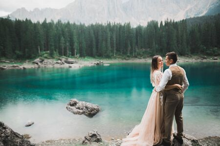 Romantic wedding moment, couple of newlyweds smiling portrait, bride and groom hugging near a beautiful lake in the mountains