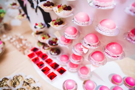 Delicious sweets on wedding candy buffet with desserts, cupcakes. Banco de Imagens