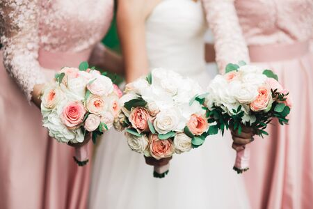 Bride with bridesmaids holding wonderful luxury wedding bouquet of different flowers on the wedding day.