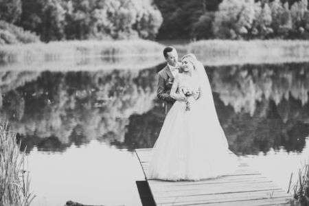 Beautiful bride and groom embracing and kissing on their wedding day outdoors Banco de Imagens