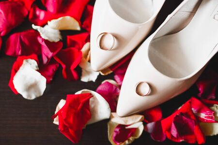Beautiful toned picture with wedding rings on wedding shoes against the background of flowers Banco de Imagens