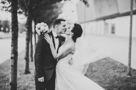 Beautiful bride and groom embracing and kissing on their wedding day outdoors Reklamní fotografie