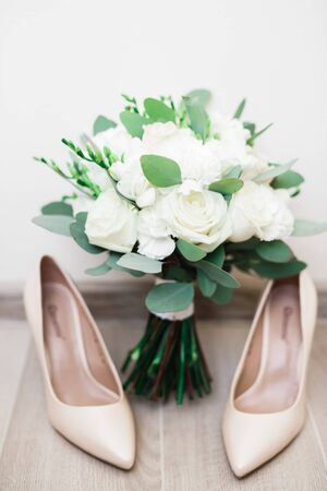 Pair of elegant and stylish bridal shoes and a bouquet of roses and other flowers