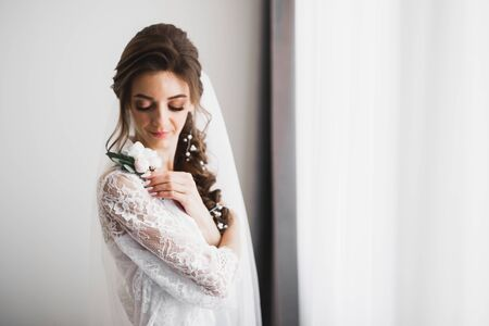 Portrait of beautiful bride with fashion veil at wedding morning