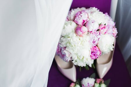 Pair of elegant and stylish bridal shoes with a bouquet with roses and other flowers. Stock fotó