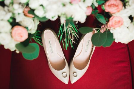 Pair of elegant and stylish bridal shoes with wedding rings and a bouquet of roses and other flowers.