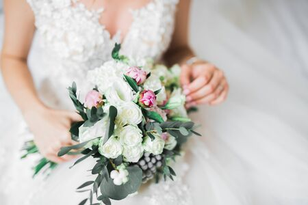 Bride holding big and beautiful wedding bouquet with flowers.