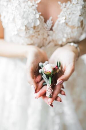 Beautiful luxury bride in elegant white dress holds bouquet of flowers in the hands.