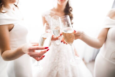 Photo bride with her friends drinking champagne from glasses. Stock fotó