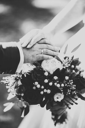 Beautiful young wedding couple posing with bouquet of flowers in hands.