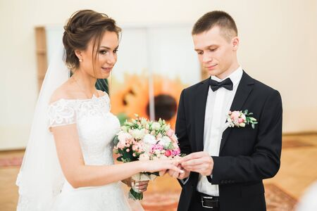 Bride and groom exchanging wedding rings. Stylish couple official ceremony Stock fotó