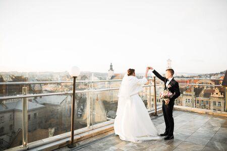 Beautiful wedding couple dancing on a balcony.