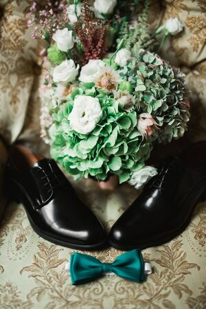Set of mans fashion shoes and beautiful wedding bouquet with different flowers, roses.