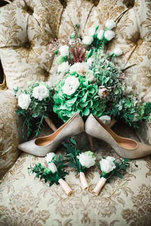 Pair of elegant and stylish bridal shoes and a bouquet of roses and other flowers. Stock fotó