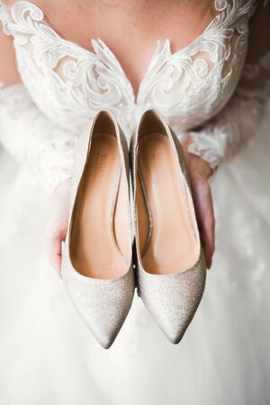 Beautiful luxury bride in elegant white dress holds wedding shoes in the hands.