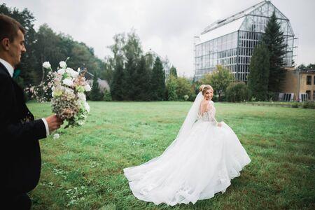 Romantic wedding moment, bride running from groom in a park Stock fotó
