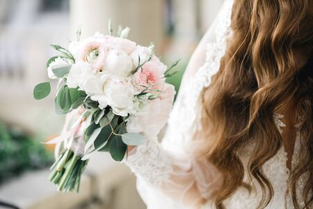 Portrait of stunning bride with long hair posing with great bouquet.