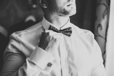 Grooms morning preparation. Handsome man getting dressed and preparing for the wedding. Stock fotó