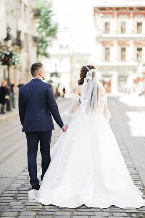 A loving wedding couple are walking back along the streets of the city of Lviv. Stock fotó