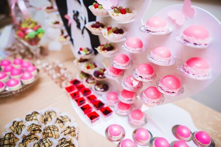 Delicious sweets on wedding candy buffet with desserts, cupcakes. 免版税图像