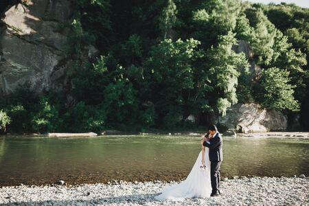Wedding couple, groom and bride hugging, outdoor near river.