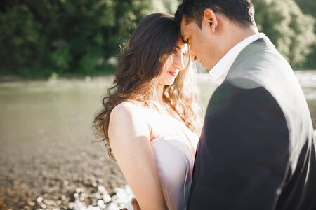 Romantic wedding moment, couple of newlyweds smiling portrait, bride and groom hugging.