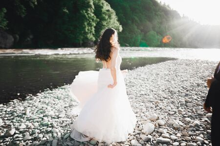 Beauty portrait of bride wearing fashion wedding dress with feathers with luxury delight make-up and hairstyle.