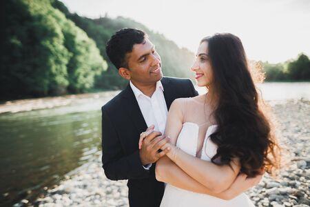 Wedding couple, groom and bride hugging, outdoor near river