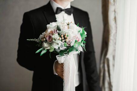 Beautiful man, groom holding big and beautiful wedding bouquet with flowers. 免版税图像
