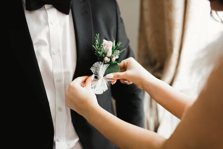 Happy groom posing with boutonniere. 免版税图像