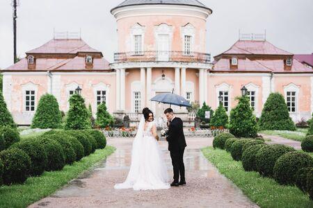 Happy wedding couple walking in a botanical park under umbrella while raining..