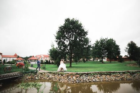 Happy wedding couple. Bride running from groom in a botanical park.