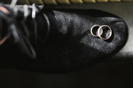 Set of mans fashion shoes with two golden wedding rings. 写真素材
