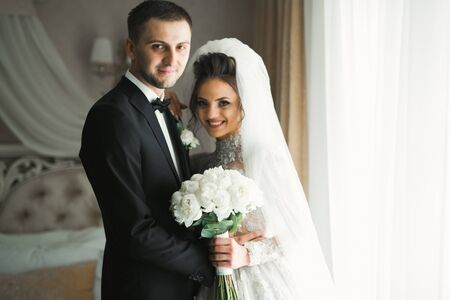 Romantic wedding moment, couple of newlyweds smiling portrait, bride and groom hugging