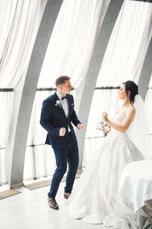 Happy beautiful newlyweds dancing near big windows