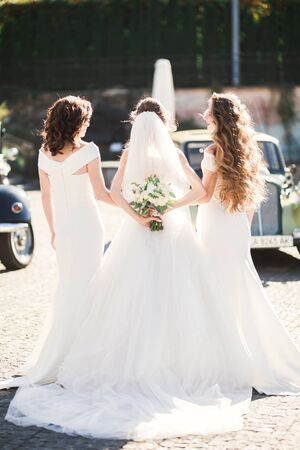 Bride with bridesmaids holding wonderful luxury wedding bouquet of different flowers on the wedding day