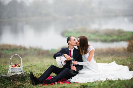 Beautiful bride and groom embracing and kissing on their wedding day outdoors Standard-Bild