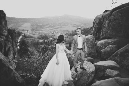 Beautiful gorgeous bride posing to groom and having fun near at mountains with amazing view, space for text, wedding couple