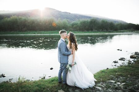 Elegant stylish happy blonde bride and gorgeous groom on the background of a beautiful river in the mountains.