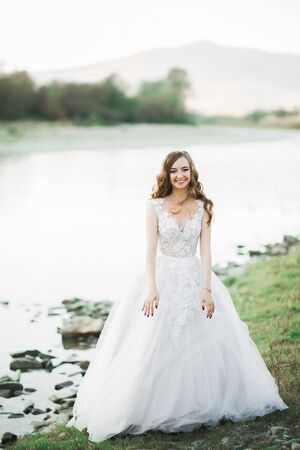 Beautiful brunette bride in elegant white dress posing near river Banque d'images