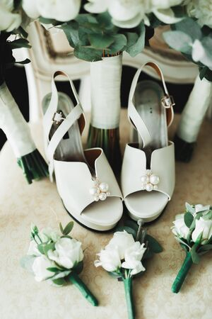 Pair of elegant and stylish bridal shoes with a bouquet with roses and other flowers