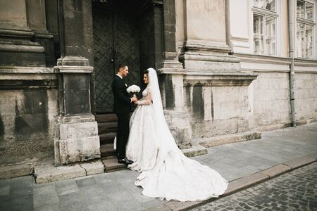 Lovely happy wedding couple, bride with long white dress posing in beautiful city.