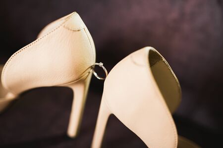 Beautiful toned picture with wedding rings and wedding shoes.