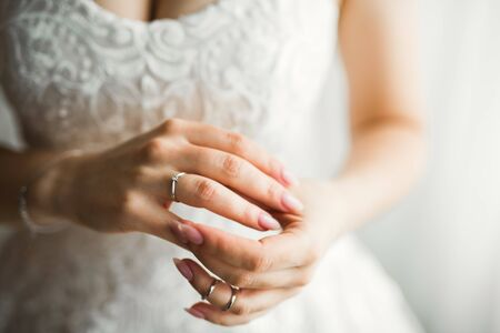 Beautiful luxury bride in elegant white dress holds wedding rings in the hands, Imagens