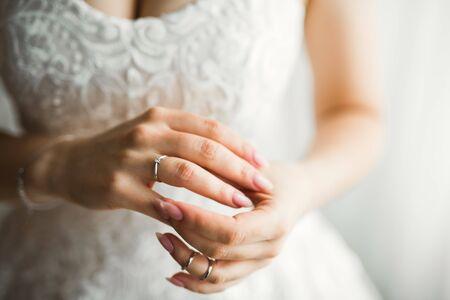 Beautiful luxury bride in elegant white dress holds wedding rings in the hands, Standard-Bild