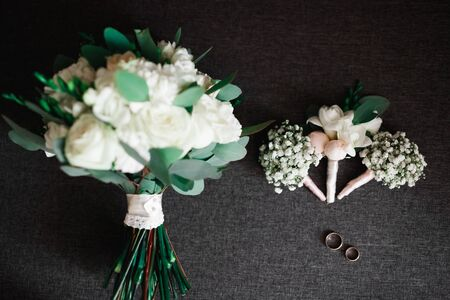 Wedding rings and a bouquet of roses and other flowers.