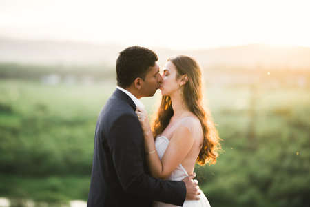 Beautiful bride and groom embracing and kissing on their wedding day outdoors Archivio Fotografico